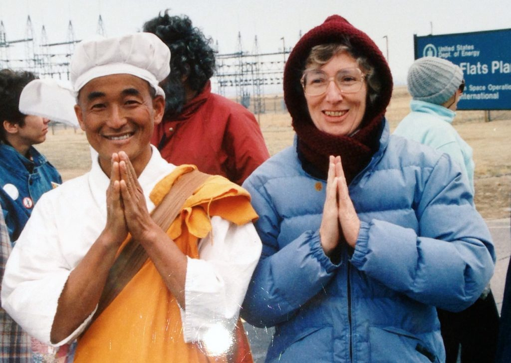 Dressed in a warm hat and coat, Pat McCormick stands next to a Buddhist monk; both their hands are folded in prayer/greeting.