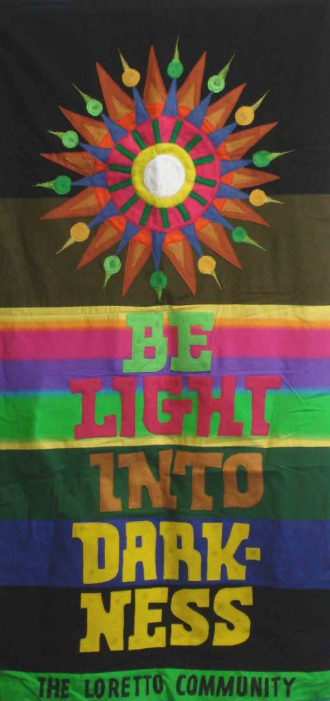 "Banner designed by Robert Strobridge with starburst and phrase ""Be Light Into Darkness."""