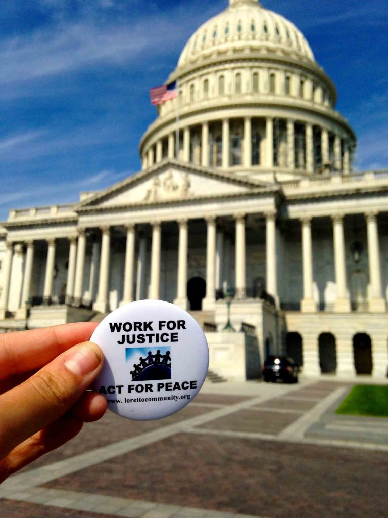 "Button with ""Work for Justice, Act for Peace"" in front of the US capitol."