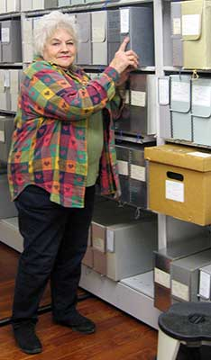 Heritage Center Assistant Marcia Mohin relocates file boxes on the new moveable shelves. (Photo courtesy of Eleanor Craig)
