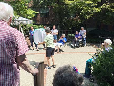 As Motherhouse residents applaud, Joyce Minkler releases monarch butterflies onto the Motherhouse grounds.