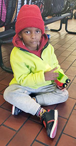 A young boy plans with his toy at the bus station. (Photo courtesy of the Rev. Jim Flynn)