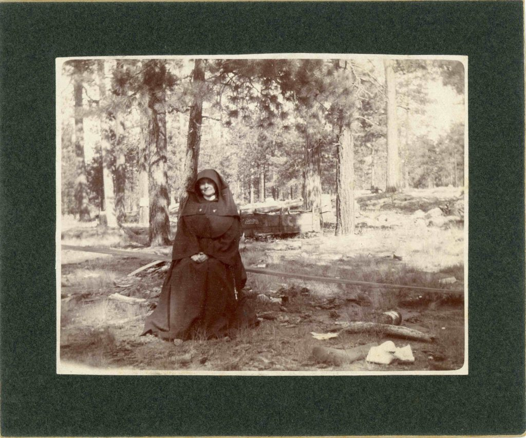 Sister M. Victor McCormick sitting in the woods.