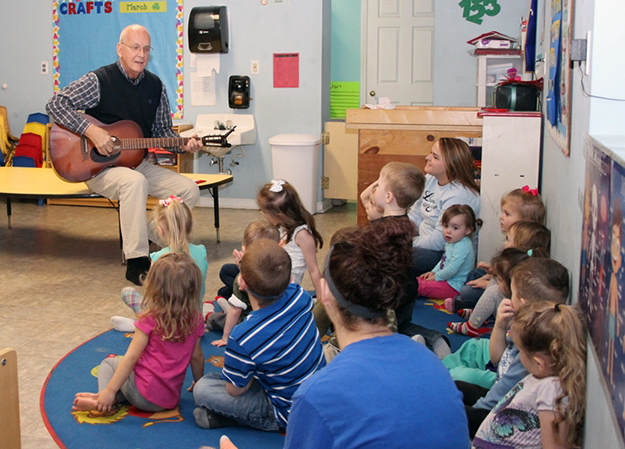David Edwards plays guitar for elementary students