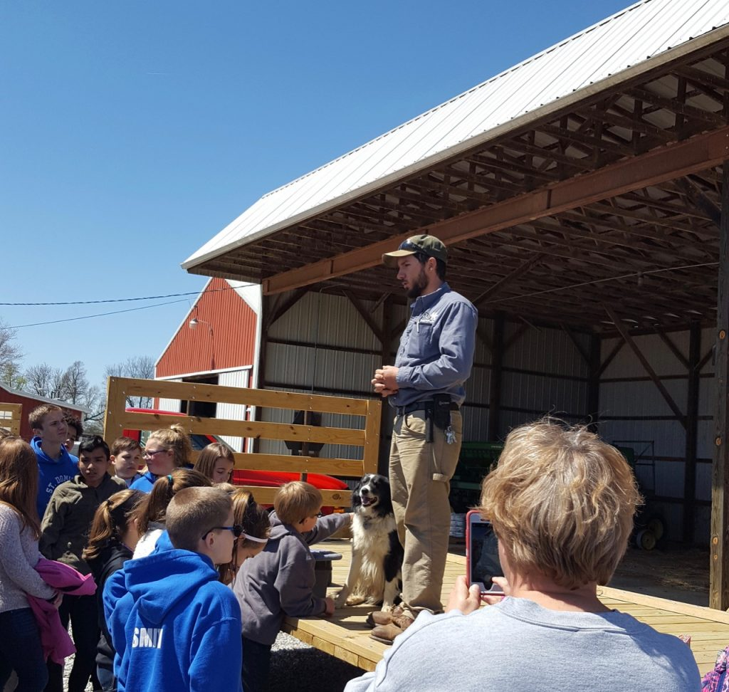 Students gather and listen to man standing on a hayrack.