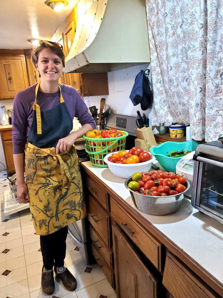 Woman standing by counter full of ripe tomatoes