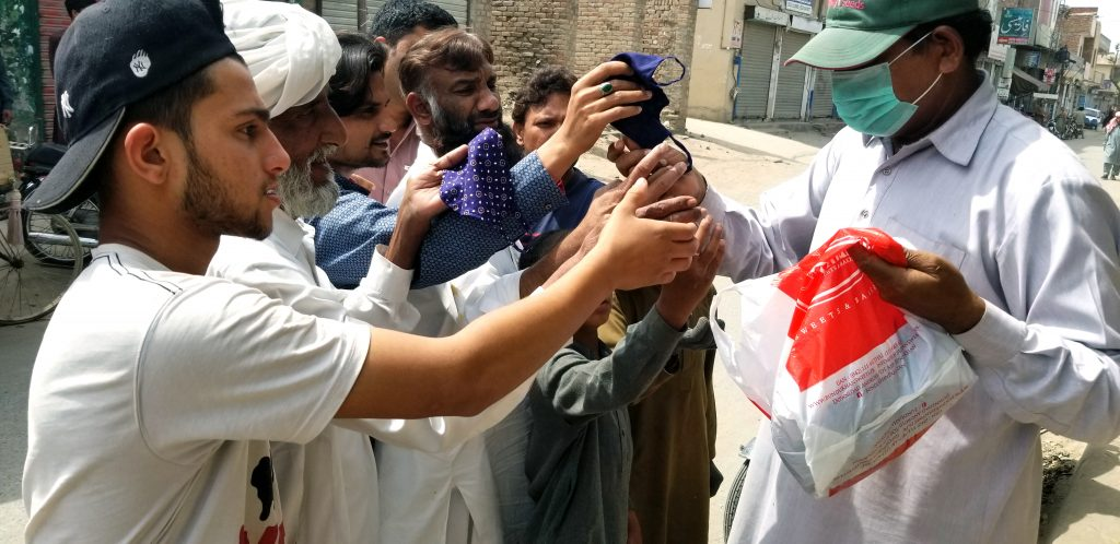 Group of men being given masks