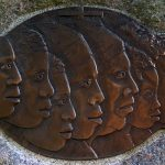 Carved faces on a bronze plate mark the Slave Memorial at the Loretto Motherhouse.
