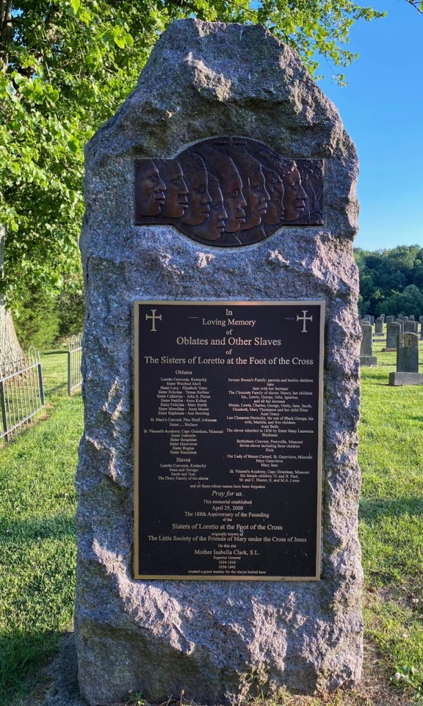 """Stone memorial with bronze plaque that reads """"In Loving Memory of Oblates and Other Slaves of The Sisters of Loretto at the Foot of the Cross"""""""