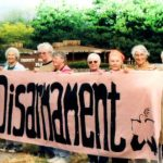 "Loretto Community members wearing sackcloth stand by the sidewalk with a banner that reads ""Loretto Women for Disarmament."""