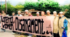 """Loretto Community members wearing sackcloth stand by the sidewalk with a banner that reads """"Loretto Women for Disarmament."""""""