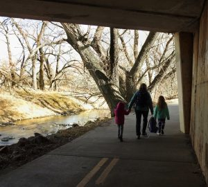 A woman and two children pass through an overpass on a paved path next to a creek.