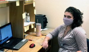 A young woman in a mask sits at her desk in front of a laptop.