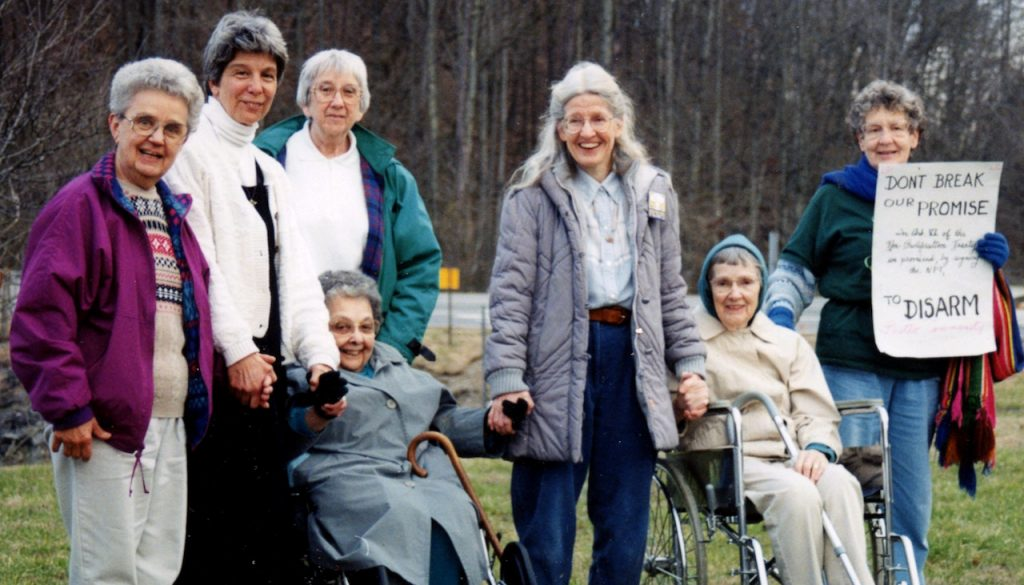 """A group of women standing and in wheelchairs stand together holding a sign that reads """"Don't Break Our Promise To Disarm."""""""