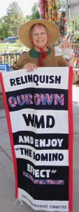 """Woman in hat stands in front of strands of paper cranes and holds banner reading """"Relinquish our own WMD and enjoy """"The Domino Effect."""""""