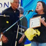 Mary Ann McGivern SL stands at a microphone and presents an award to Bishop Tom Gumbleton