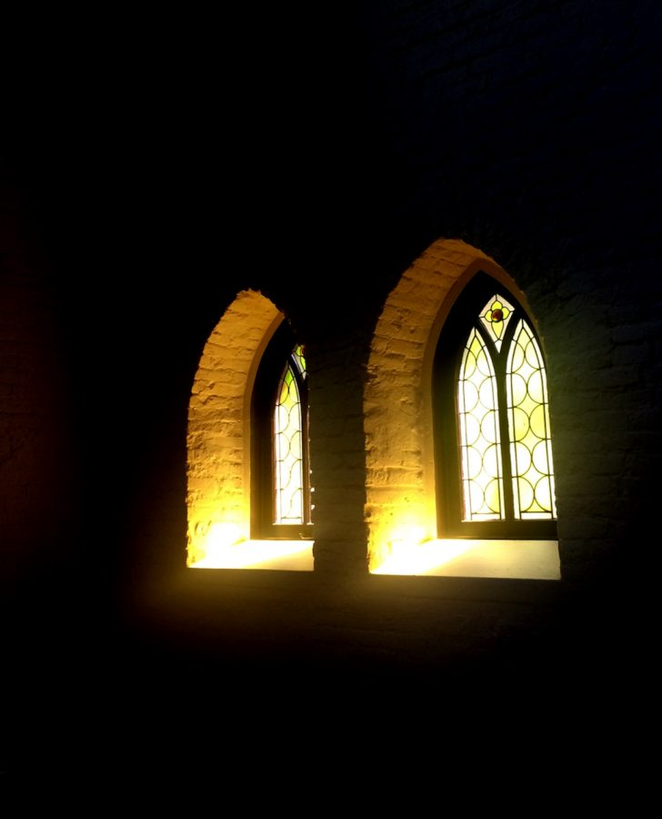 Light streams through two simple stained glass windows into a dark room.