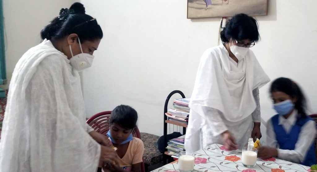 Two Pakistani women in white habits and masks feed two young Pakistani girls at a table.