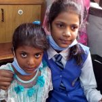 Two young Pakistani girls, one in a school uniform and one in a lacey dress, sit together.
