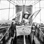 "Marchers carry a banner as they cross a pedestrian bridge. The banner reads ""The Great Peace March for Global Nuclear Disarmament."""