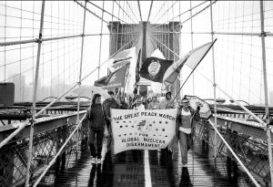 """Marchers carry a banner as they cross a pedestrian bridge. The banner reads """"The Great Peace March for Global Nuclear Disarmament."""""""