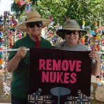 "Two women in hats and sunglassed hold a ""Remove Nukes"" banner in front of strands of paper cranes."