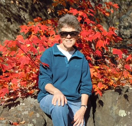 Woman sits on a rock outcropping with a beautiful spread of red leaves behind her.