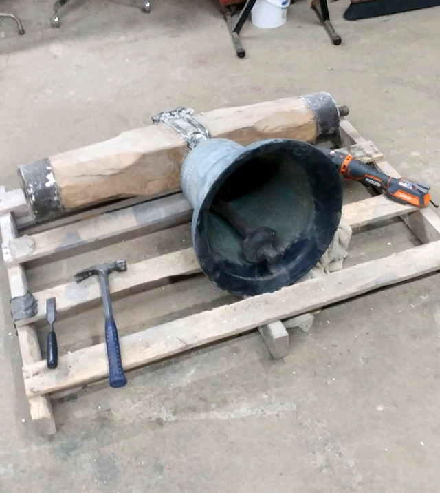 A large bell attached to a beam sits on a wooden pallet with several tools around it.