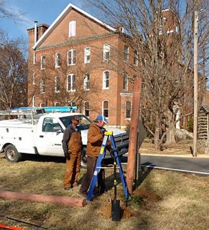 Two men in work clothes position a ladder near a wooden pole. A white work truck and a building are in the background.