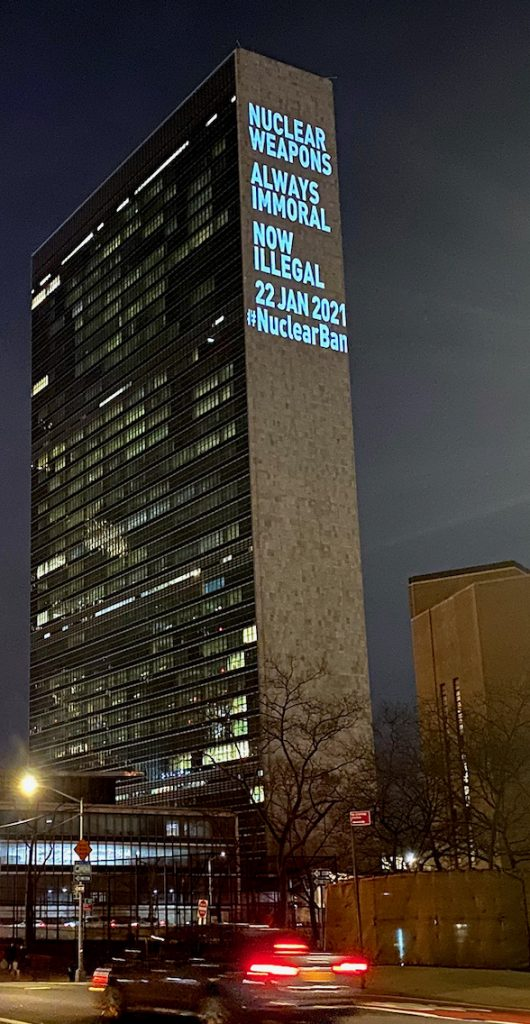 "A tall office building displays the words ""Nuclear Weapons Always Immoral Now Illegal 22 Jan 2021 #NuclearBan"" on its side."