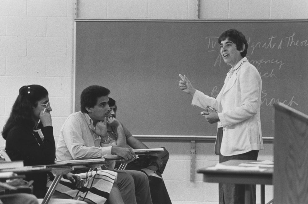 A woman stands at the front of a blackboard. Three students sit in desks, listening to her lecture.