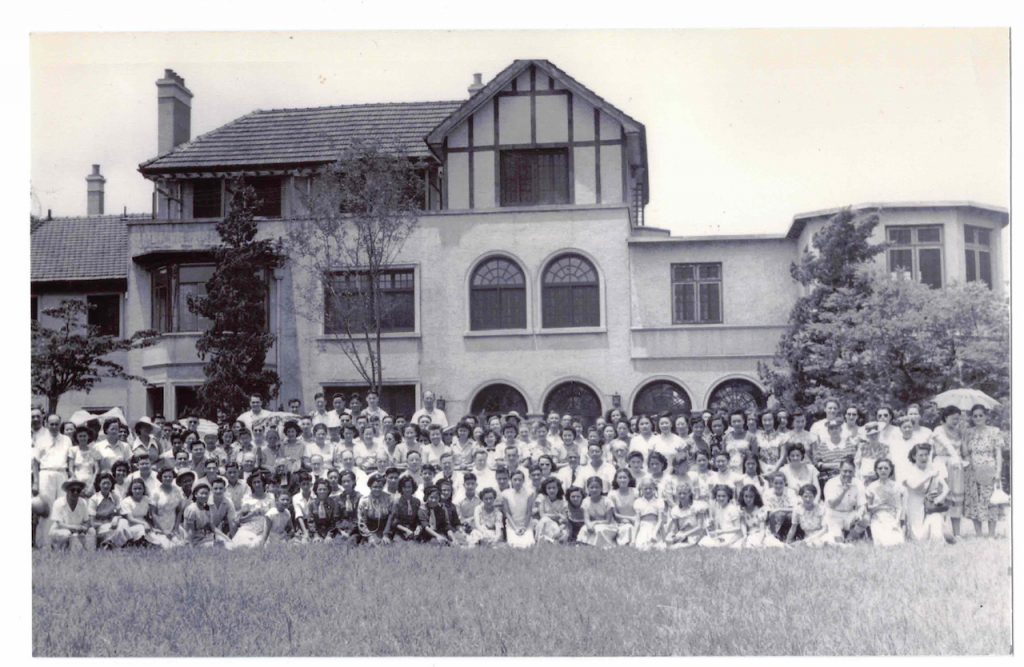 Archival photo of a large group of people posing for a photo in front of a building
