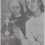 A historical newspaper photo of a nun in habit and a woman in glasses each holding the same standard.