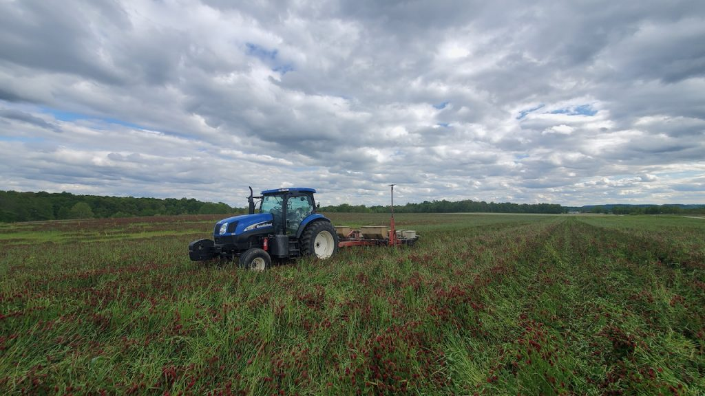 A tractor sits in the middle of a field with dramatic clouds above.