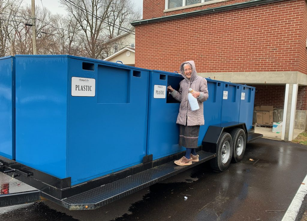 A woman stands near large recycling container, demonstrating how to recycle.