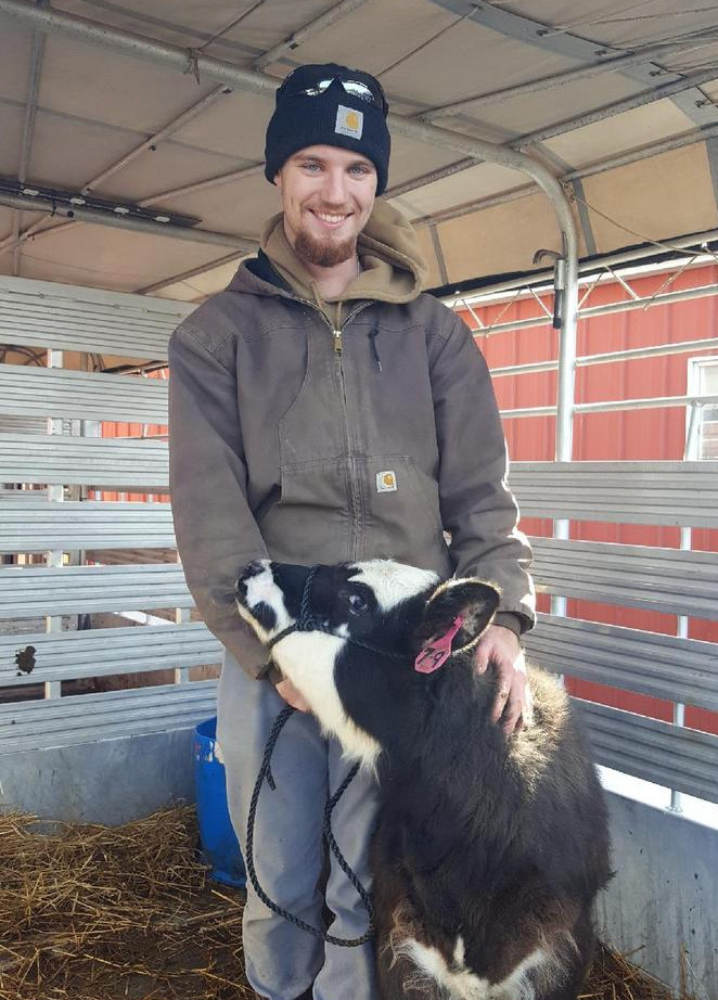 A smiling man holds the head of a black and white calf.