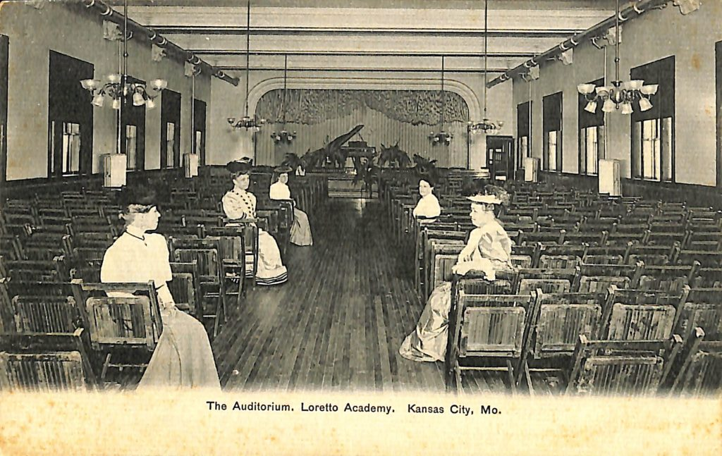 Historical photo of several women sitting in chairs in an auditorium.