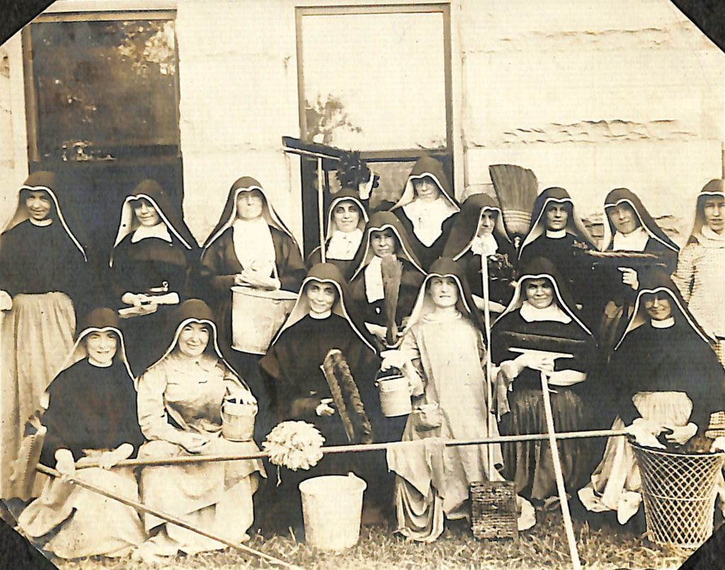 Historical photo of group of Sisters of Loretto sitting outside with cleaning supplies and implements