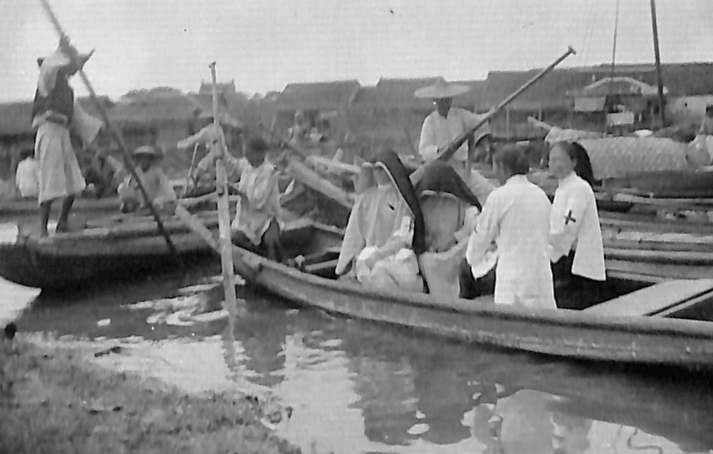 Archival photo of sisters in habit in a punt boat in canal traffic.