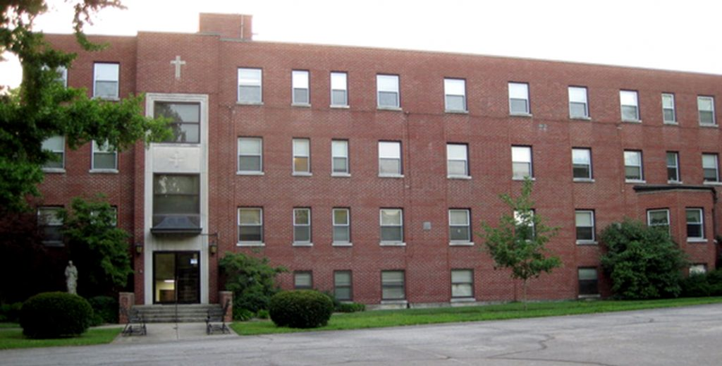 Long, four story brick building with a cross above the entrance.