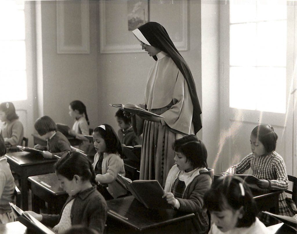 Historical photoo of a sister in habit reading to her students while walking between rows of desks.