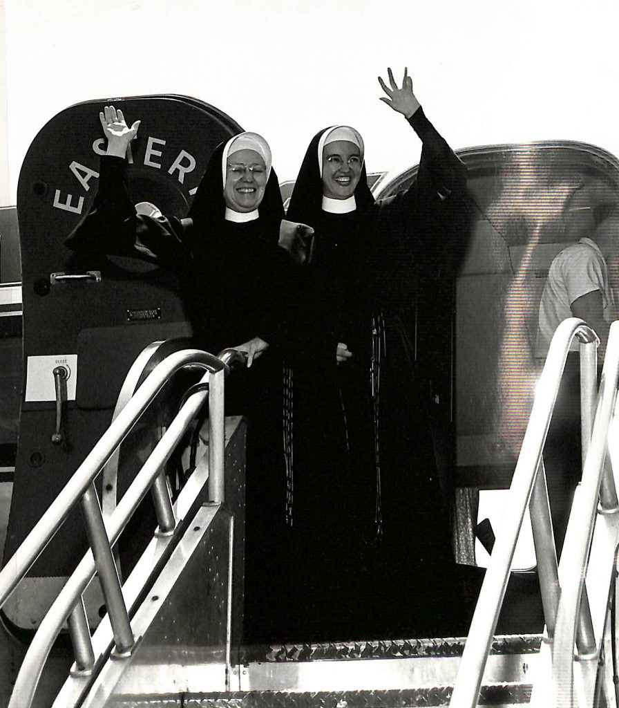 Archival photo of two sisters in habit waving from the door of a plane.