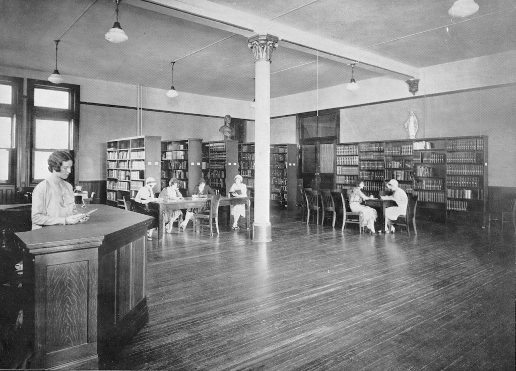 Archival photo of inside Loretto Heights College library with shelves of books and students reading at tables.