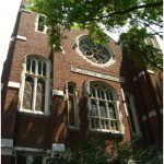 """Looking up at a large brick building with """"Loretto College"""" carved across the front, under an ornate rose window."""