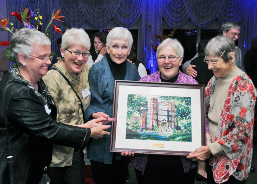 Women beaming with smiles hold a painting of Webster University building