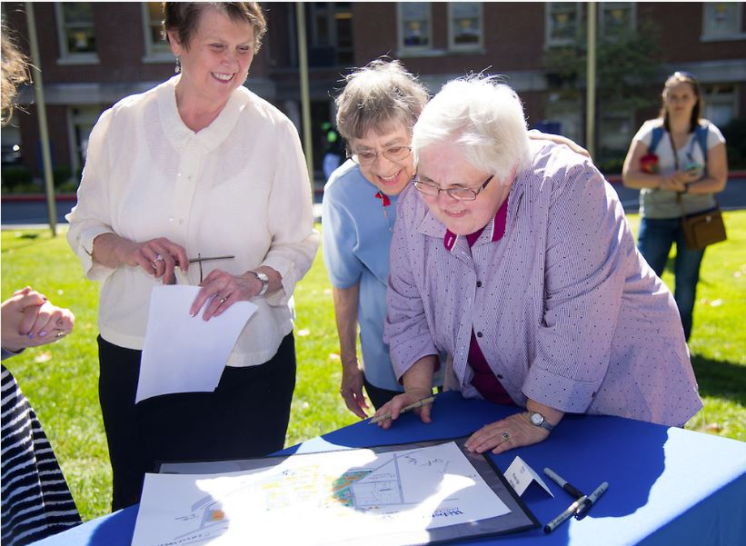 Three women stand outside looking at a drawing on a table.