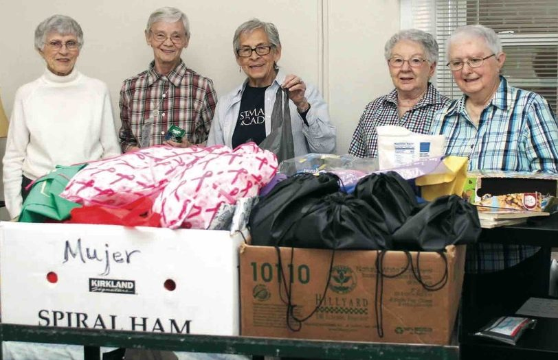 Five women stand behind boxes of donated clothes.