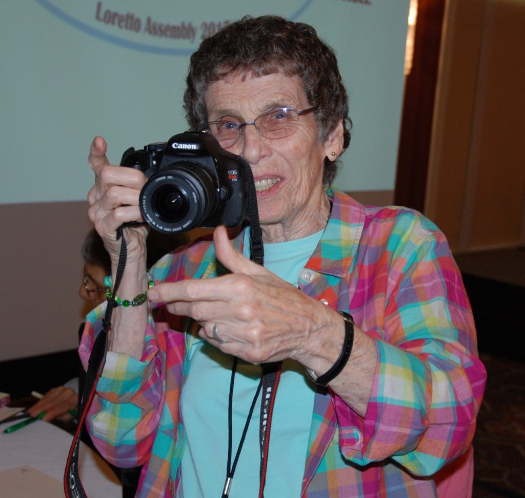 A woman smiles from behind her camera.