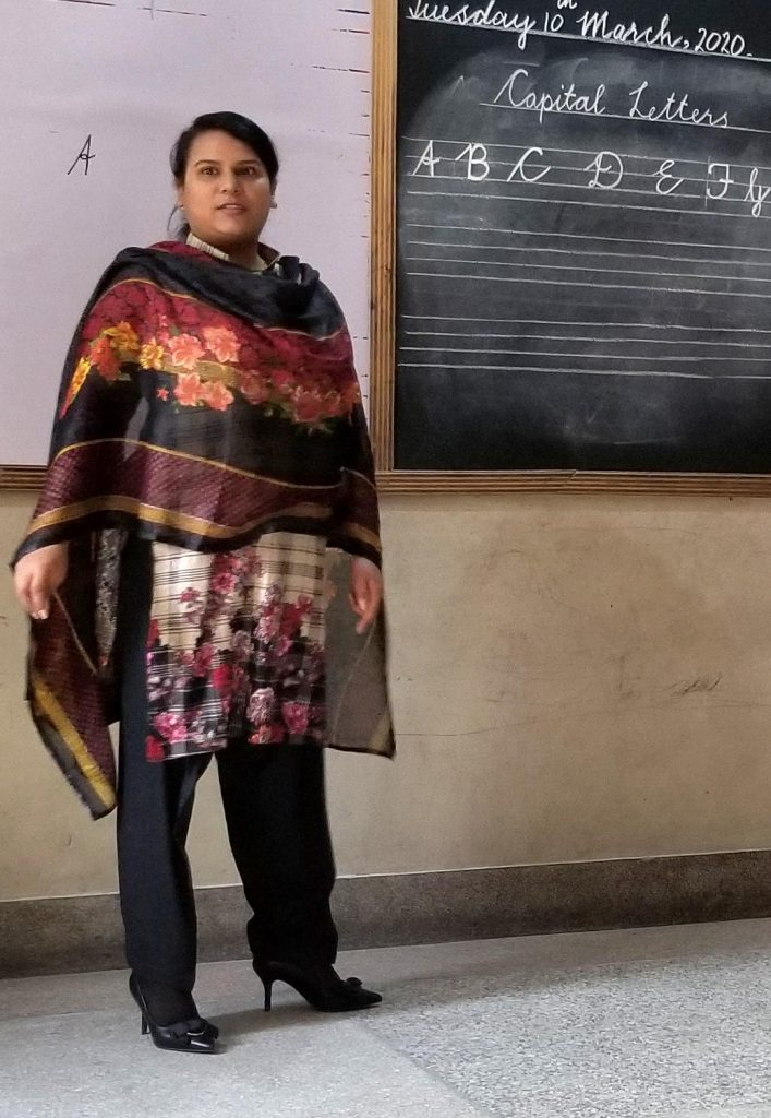 A Pakistani woman stands in the front of a classroom.