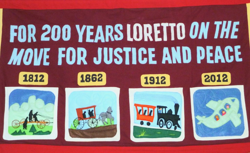 """Banner reads """"For 200 years Loretto on the move for justice and peace."""""""